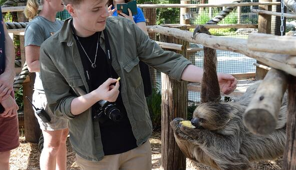 Young man feeding a sloth in the animal encounters at Wild Florida